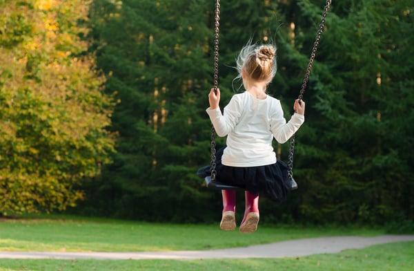 girl-on-swing-in-backyard-garden